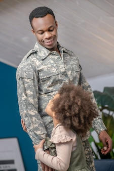 Positive communication. dark skinned curly little girl and young smiling dad in military uniform standing at home looking at each other