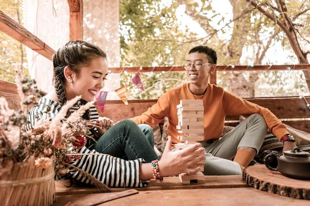긍정적 인 의사 소통. 행복 한 젊은 남자가 나무 집에 있고 그의 여자 친구를보고