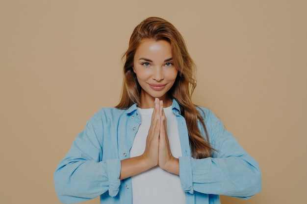Positive concentrated young woman holding palms together in prayer gesture, being calm and peaceful, making namaste yoga sign on beige background. body language concept