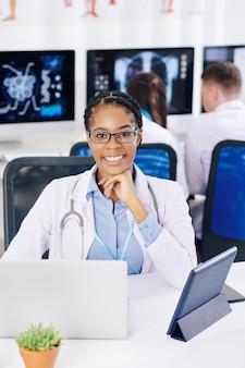 긍정적 인 자신감을 가진 아프리카 계 미국인 일반 개업의가 실험실에서 그녀의 책상에 앉아 컴퓨터에서 작업