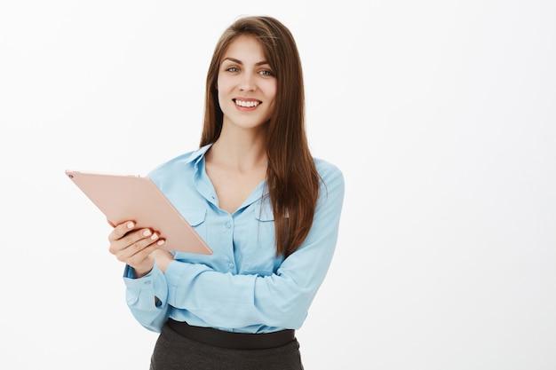 Positiva donna di affari bruna fiduciosa posa in studio