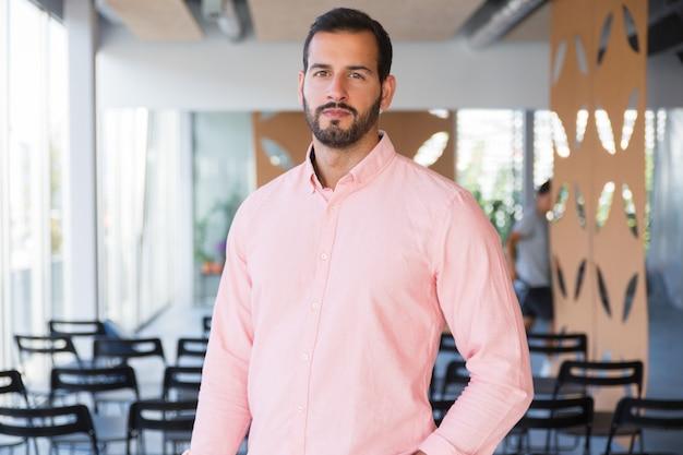 Положительный уверенно бизнес-тренер позирует в тренажерном зале