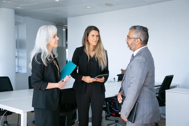 긍정적 인 자신감을 가진 비즈니스 파트너는 폴더와 태블릿을 들고 협업에 대해 회의 및 논의합니다. 측면보기. 커뮤니케이션 또는 파트너십 개념