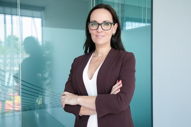 Positiva imprenditrice fiduciosa indossando abito formale e occhiali, in piedi con le braccia conserte e sorridente
