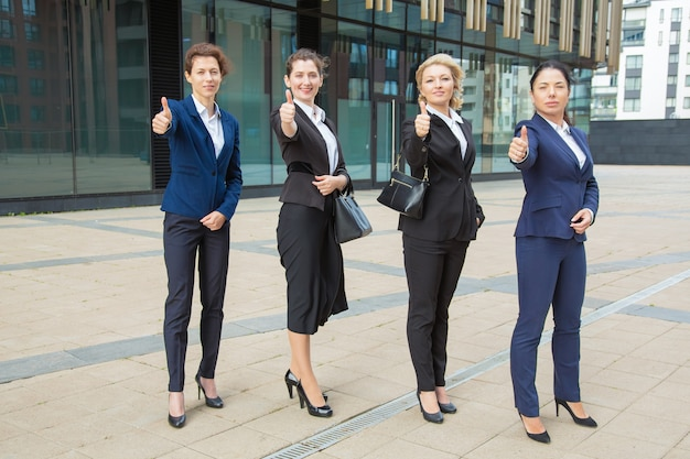 Positive confident businesswomen team standing together near office building, showing like gesture, making thumb up, looking at camera. full length. teamwork and business success concept