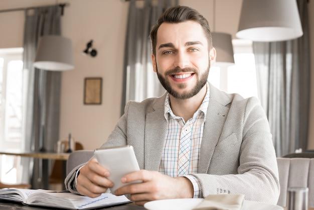 Positive confident entrepreneur in cozy restaurant