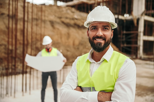 新しい建物のベースの近くに立っている間、ヘルメットとチョッキのポーズで前向きな自信を持って民族のひげを生やした男性の建設労働者
