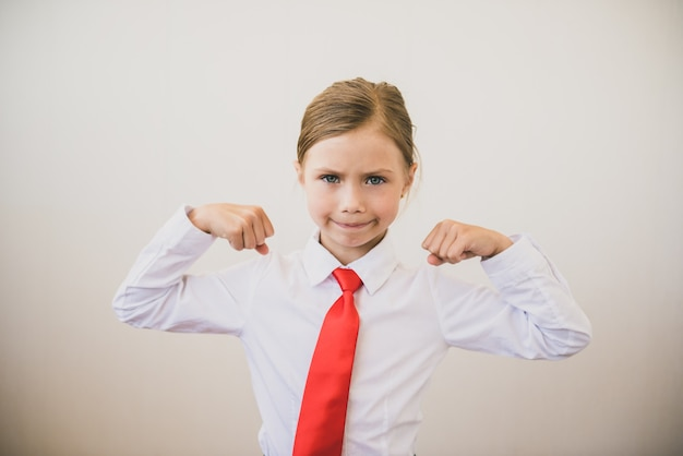 힘을 보여주는 긍정적 자신감 페미니스트. 팔뚝 flexing 및 카메라에 미소 아름 다운 아이 소녀. 페미니즘 개념