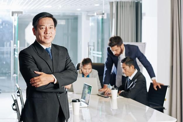 会議室のテーブルで腕を組んで立って、正面を見て前向きな自信を持って成熟したベトナムの起業家