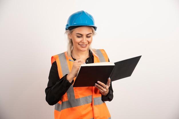ノートに書く前向きな建設労働者。高品質の写真