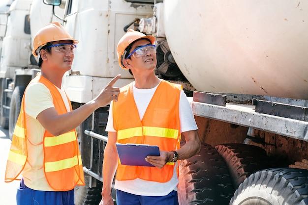 建設現場でセメントミキサートラックを駐車する場所について話し合う保護ゴーグルの積極的な請負業者...