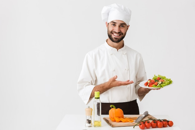 Positive cook man in uniform smiling and holding plate with vegetable salad isolated over white wall