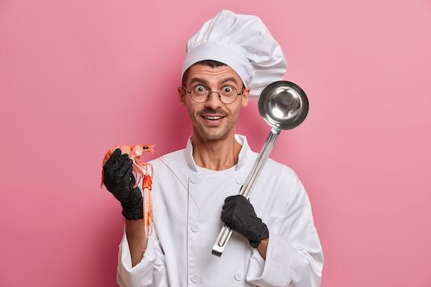 Positivo cuoco posa con gamberi crudi, mestolo d'acciaio, andando a preparare una gustosa zuppa, indossa una divisa bianca