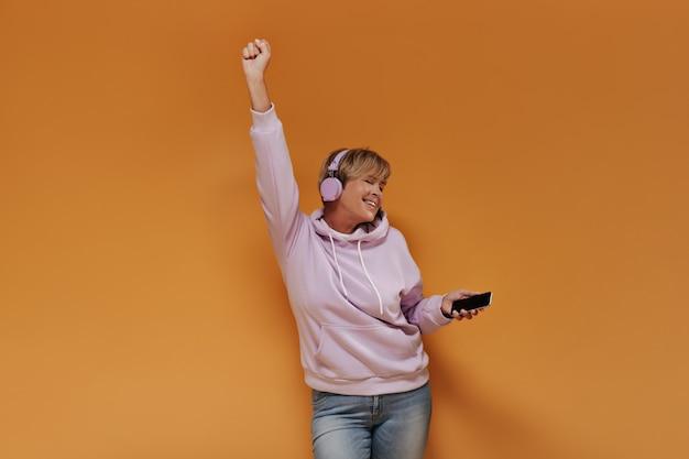 短い髪型と広いピンクのパーカーで踊り、孤立した背景で音楽を聴いているライラックのクールなヘッドフォンを持つポジティブなクールな女性。