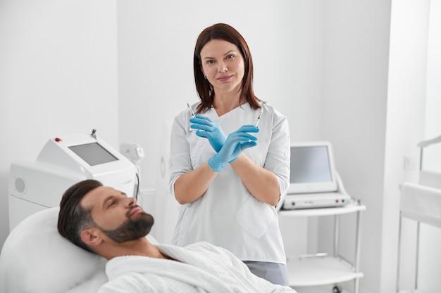 긍정적인 미용사는 미용실에서 성숙한 남자 옆에 서서 피부 리프팅을 위한 필러가 있는 주사기를 들고 있습니다