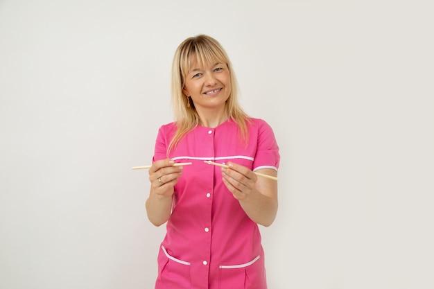 ピンクの医療ユニフォームを着たポジティブな美容師が、サロンで竹の棒を使ったマッサージ手順にあなたを招待します。小規模なビジネス。美容業界。アンチエイジング手順。ライフスタイル。リラックスできるマッサージ。