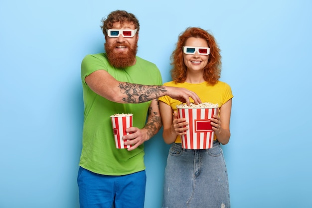 Positive couple come on late night film in cinema, eat delicious popcorn