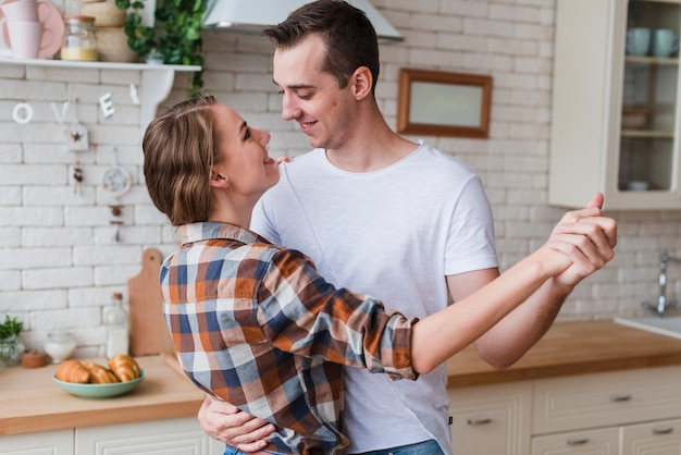 Positive couple hugging and dancing in kitchen