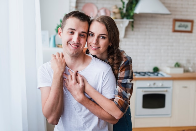 Positive couple hugging near kitchen