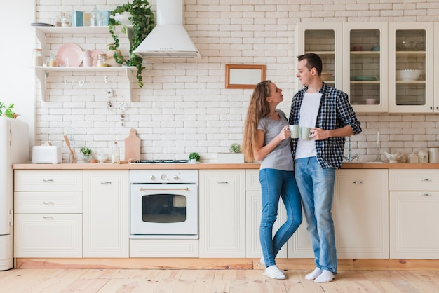 Positive couple standing in kitchen and relishing tea