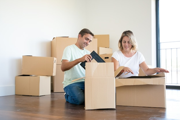 Positive couple unpacking things in new apartment, sitting on floor and taking objects from open boxes