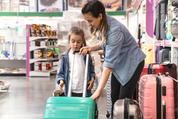 Positive couple with kid buying suitcase on wheels for vacation in a store