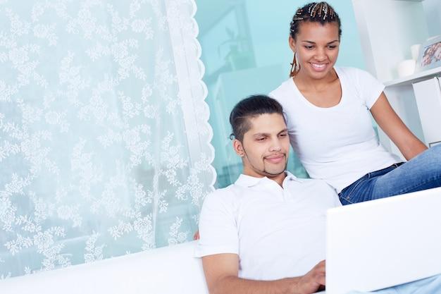 Положительная пара с ноутбуком у себя дома