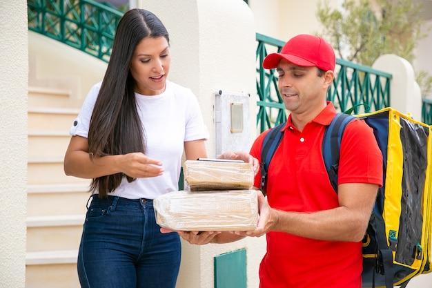 고객 문에 소포를 배달하는 긍정적 인 택배는 수령 확인을 위해 태블릿을 여성에게 제공합니다. 배송 또는 배달 서비스 개념