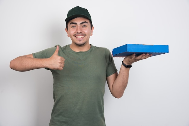 Positive courier holding pizza and showing thumbs up on white background.