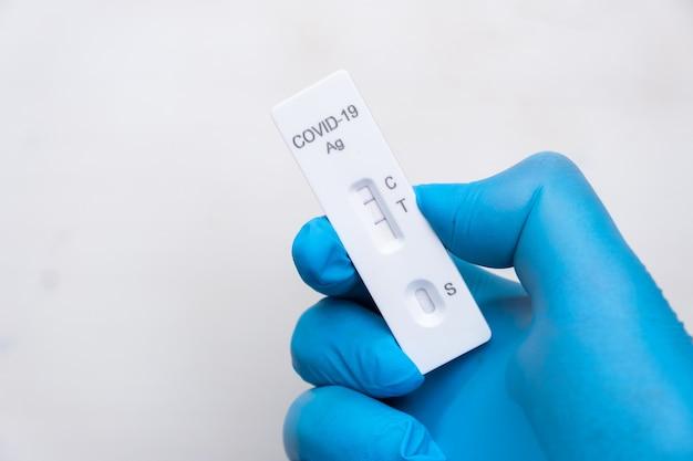 ゴム手袋をはめた医師の手で病気を迅速に検出するための陽性のcovid抗原検査
