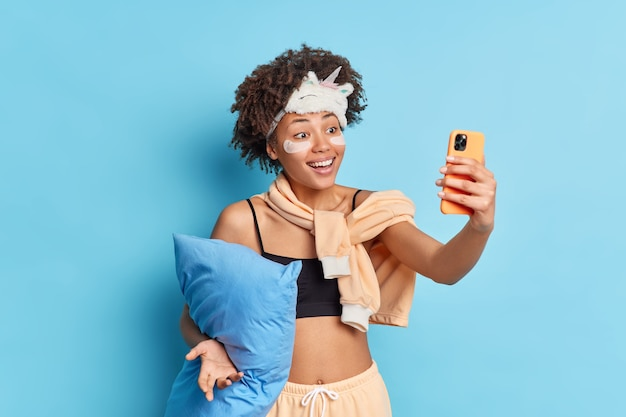Positive culry haired young afro american woman takes selfie via smartphone smiles happily applies collagen patches under eyes dressed in pajama holds pillow isolated over blue studio wall
