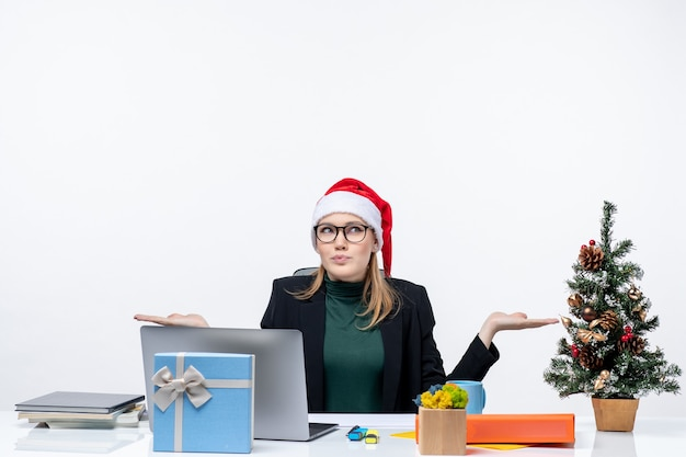 Positive curious business woman with santa claus hat sitting at a table with a xsmas tree and a gift on it on white background