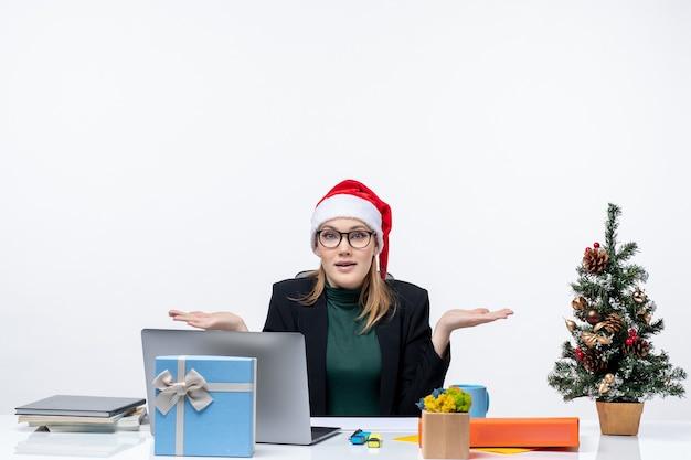 Donna d'affari interessata curiosa positiva con cappello di babbo natale seduto a un tavolo con un albero di natale e un regalo su di esso su sfondo bianco