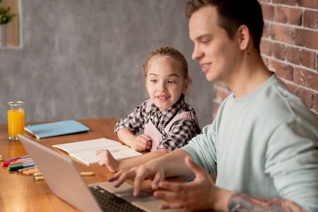 Позитивная любопытная девушка с косой сидит за столом и использует ноутбук с отцом, показывая приложение для обучения, пока они вместе выполняют творческое домашнее задание