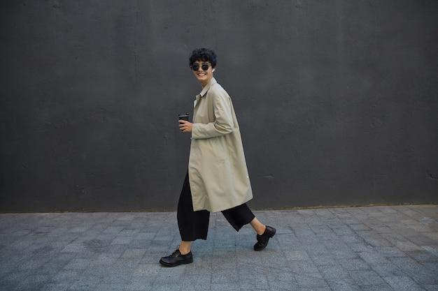 Positiva donna d'affari dai capelli scuri ricci con taglio di capelli corto che cammina sull'ambiente urbano con bicchiere di carta nero, uscire a pranzo fuori ufficio, indossare abiti alla moda e occhiali da sole alla moda