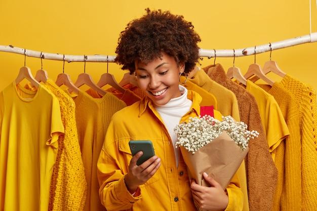 La donna etnica riccia positiva focalizzata nel dispositivo smartphone tiene un bouquet di fiori