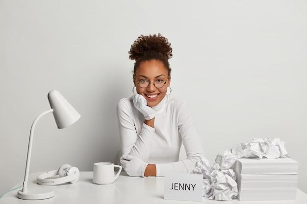 Imprenditore femminile riccio positivo lavora sul lavoro di progetto, si siede alla scrivania in ufficio bianco