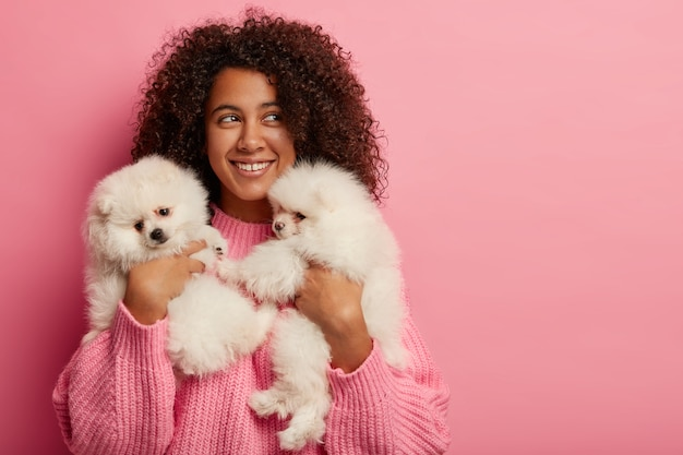 Host femmina riccia positiva felice di posare con due cuccioli di razza, ha buon umore, sorride ampiamente, esprime amore per gli animali