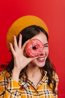 Positive curly girl winks and covers her eye with strawberry donut. attractive woman in plaid shirt and yellow hat posing on red wall.