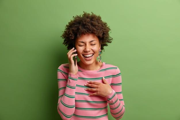 ポジティブな巻き毛の民族の女性が喜んで笑う友人と電話での会話がハングアップする緑の壁に隔離されたカジュアルなストライプのジャンパーを着ている