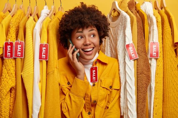 판매에 최신 유행의 옷을 구입하는 긍정적 인 곱슬 머리 아가씨, 의류 선반에 서,