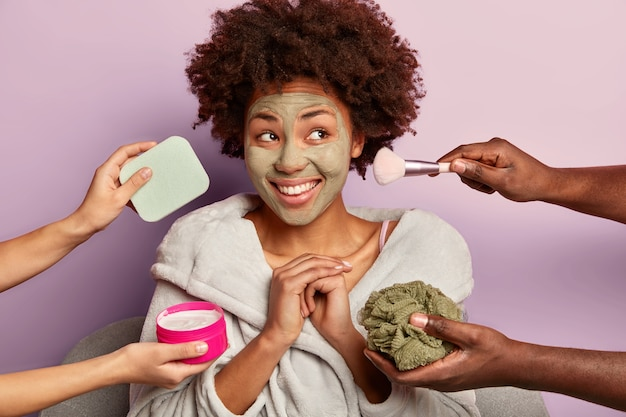 Positive curly haired woman applies facial clay mask, keeps hands together and looks with dreamy expression