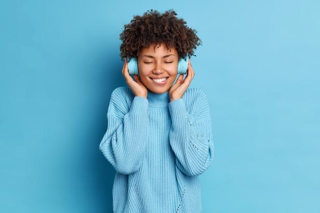 Positiva donna dai capelli ricci morde le labbra sta con gli occhi chiusi ampio sorriso gode di melodia preferita in cuffie stereo con un suono di buona qualità indossa maglione lavorato a maglia