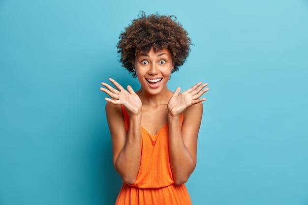 좋은 소식을 받아 기뻐하는 긍정적 인 곱슬 머리 여자는 손바닥 미소를 널리 퍼뜨립니다. 파란색 벽 위에 고립 된 세련된 주황색 드레스를 입습니다.