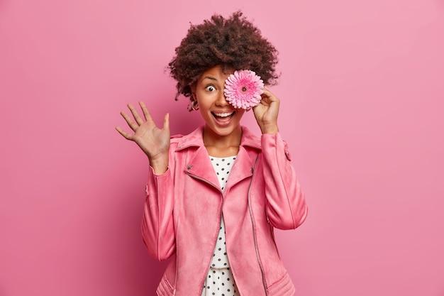ポジティブな巻き毛の女性は花屋のキャリアを持ち、ピンクのガーベラを持ち、目を花で覆い、スタイリッシュなジャケットを着て、屋内でポーズをとり、愚かで、心地よい香りを楽しんでいます。花、香り
