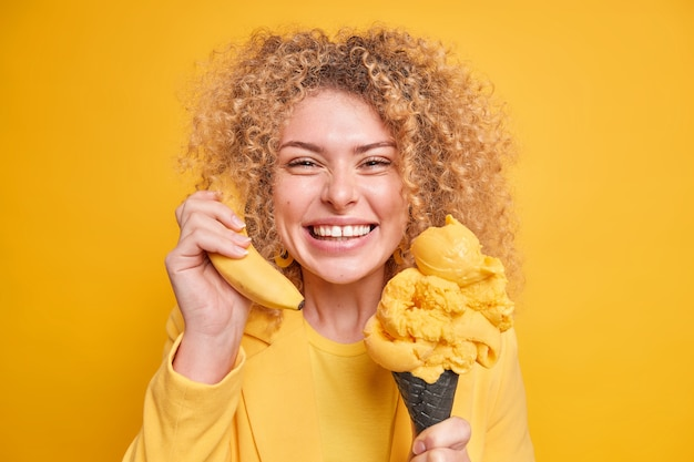 Positive curly haired woman has fun enjoys eating delicious ice cream of lemon flavor keeps banana near ear pretends calling someone expresses positive emotions isolated over yellow wall