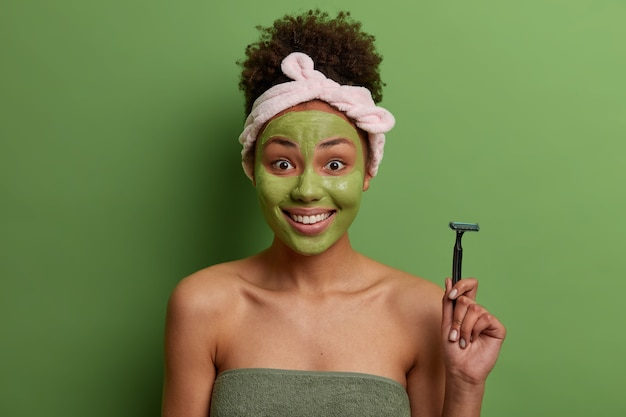 Positive curly haired woman holds razor, going to shave legs, applies moisturizing mask on face, cares about herself, wrapped in bath towel, isolated over green wall. wellbeing, purity, hygiene