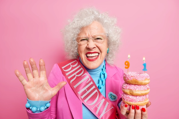 Positive curly haired woman pensioner raises palm feels very happy holds pile of glazed doughnuts celebrates 91st birthday wears festive clothes