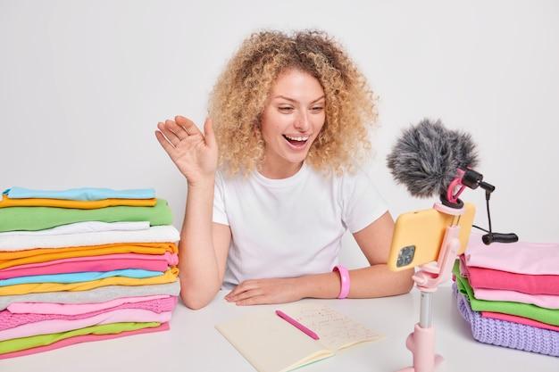 Позитивная кудрявая женщина машет подписчикам, широко улыбается, ведет собственный блог о домашних делах, носит повседневную футболку, позирует вокруг груд сложенной одежды, изолированной на белом