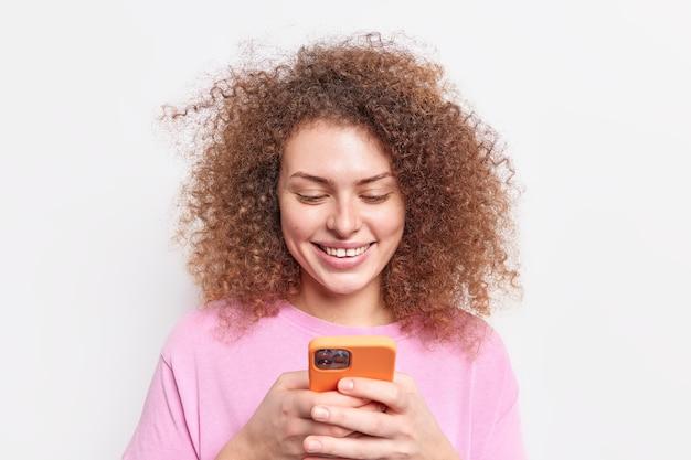 Позитивная кудрявая молодая европейская женщина улыбается, нежно держит современные чаты на смартфоне в социальных сетях, подключается к беспроводному интернету, одетая в повседневную одежду, изолированную на белой стене, использует приложение